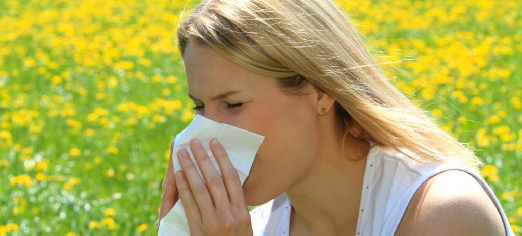 Woman sitting in meadow and blowing nose
