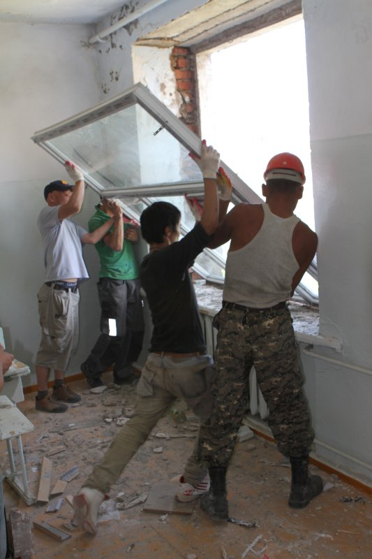 Members of the Mongolian Armed Forces 338 Construction & Engineering Unit and Mongolian contractors install a new window during renovation work on the Erdmiin Oyun School July 25, 2013, in Ulaanbaatar, Mongolia, as part of exercise Khaan Quest 2013. Khaan Quest is an annual multinational exercise sponsored by the U.S. and Mongolia, and it is designed to strengthen the capabilities of U.S., Mongolian and other nations? forces in international peace support operations. (U.S. Marine Corps photo by Sgt. John M. Ewald/Released)