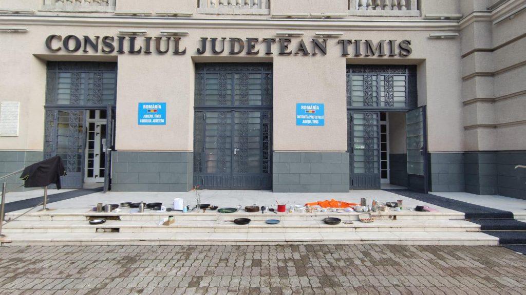 Protest pe treptele Prefecturii Timiș cu tacâmuri, pahare, tigăi și bonete ale bucătarilor/FOTO